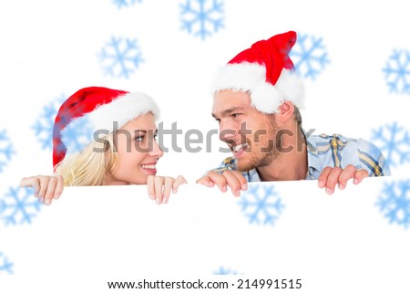Festive couple smiling from behind poster against snowflakes - stock photo