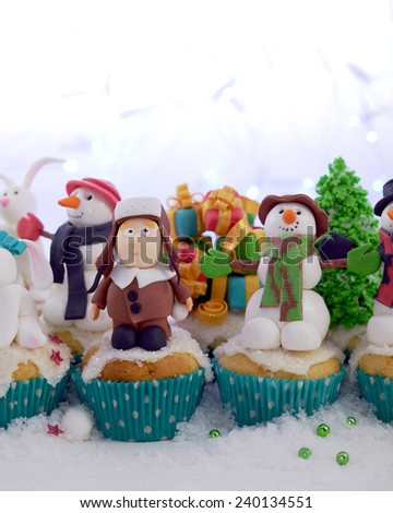 Festive cupcakes decorated with sugar figures of a kid in a fur hat and Snowman selective cropping.