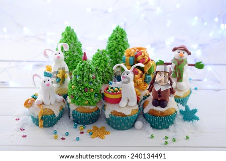Festive cupcakes with sugar figures on a bright lights background horizontal format. Three rabbits  and a kid in a fur hat decorating the Christmas tree.