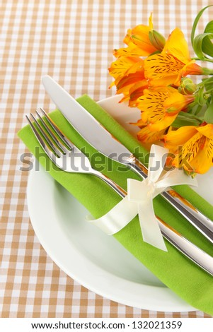 Festive dining table setting with flowers on checkered background - stock photo