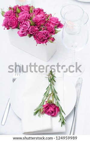 Festive dining table setting with pink roses, white tablecloths and napkins, candles, holiday dinner. - stock photo