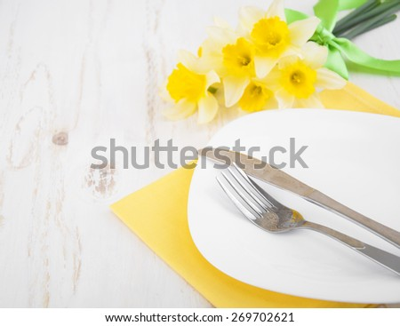 Festive dining table setting with spring narcissus flowers on wooden background  - stock photo