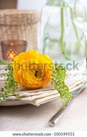 festive dining table setting with yellow-orange flowers ranunkulus - stock photo