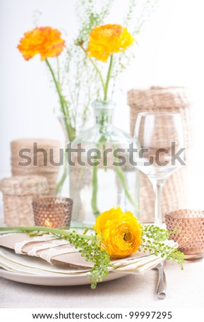 festive dining table setting with yellow-orange flowers ranunkulus - stock photo