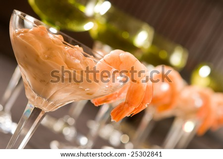 Festive dinner setting with shrimp cocktails and white wine - stock photo