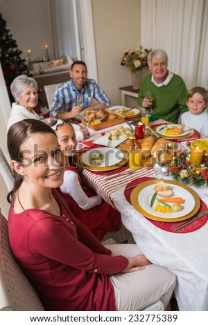 Festive family smiling at camera during christmas dinner at home in the living room - stock photo