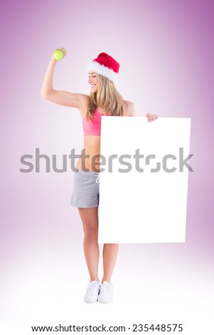 Festive fit blonde showing poster on vignette background - stock photo