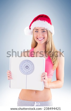 Festive fit blonde showing scales on vignette background - stock photo