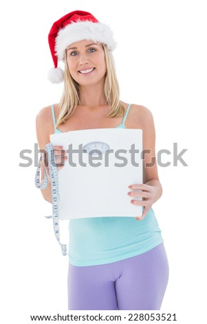 Festive fit blonde showing scales on white background - stock photo