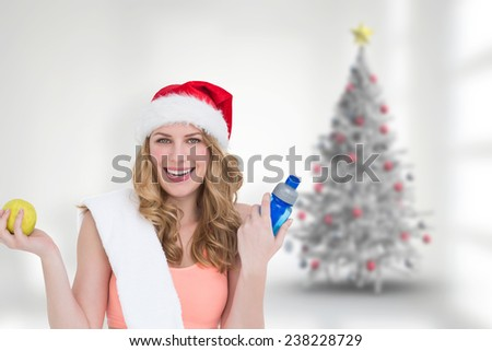 Festive fit blonde smiling at camera against blurry christmas tree in room - stock photo