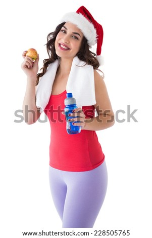 Festive fit brunette holding bottle and apple on white background - stock photo