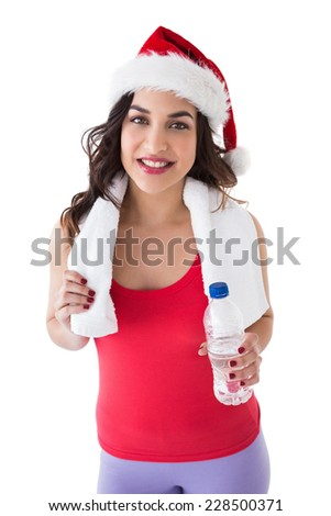 Festive fit brunette holding bottle on white background - stock photo