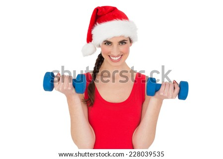 Festive fit brunette holding dumbbells on white background - stock photo