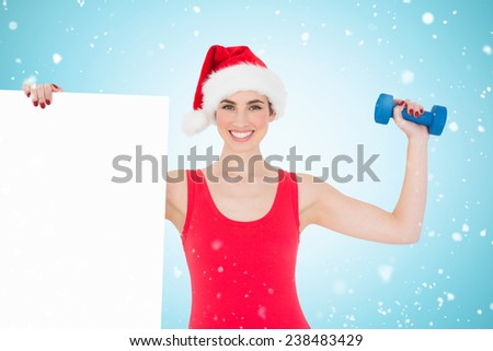 Festive fit brunette holding page and dumbbell against blue vignette - stock photo