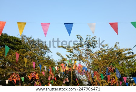 Festive flags against blue sky and tree - stock photo
