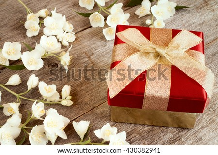 Festive gift box  and blooming flowers on wooden background - stock photo