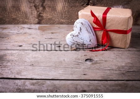 Festive gift box  and decorative red  heart on  vintage  wooden background. Selective focus. Place for text. - stock photo