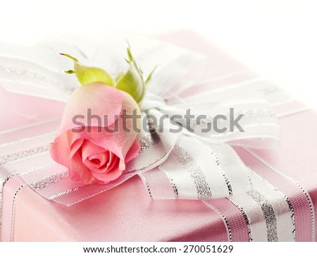 Festive gift box with a silver bow and pink rose. Elegant gift. - stock photo