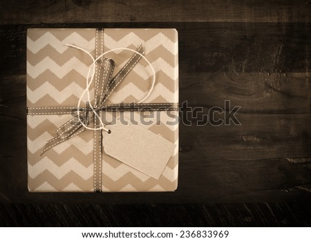 Festive gift box with chevron stripe wrapping on dark recycled wood table in sepia tones. - stock photo