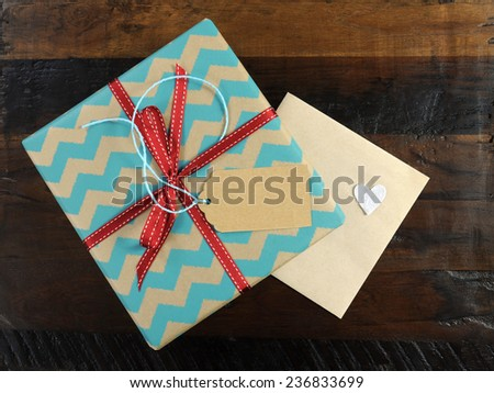 Festive gift box with chevron stripe wrapping on dark recycled wood table with gift card envelope. - stock photo