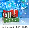 festive gift boxes against glowing christmas tree - stock photo