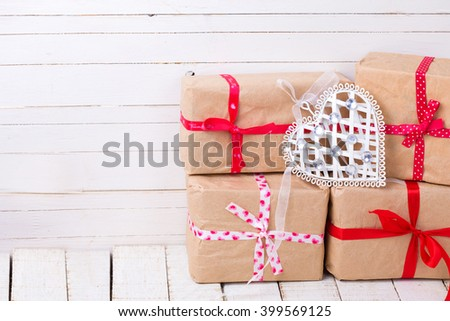 Festive gift boxes  and decorative  white heart on white wooden background. Selective focus. Place for text. - stock photo
