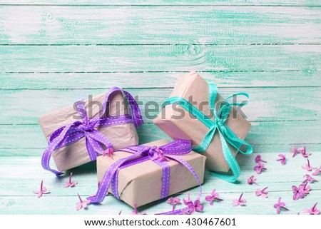Festive gift boxes and  lilac flowers on turquoise wooden background. Selective focus. Place for text. - stock photo