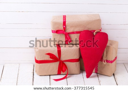Festive gift boxes and red decorative heart  on white wooden background. Selective focus.
