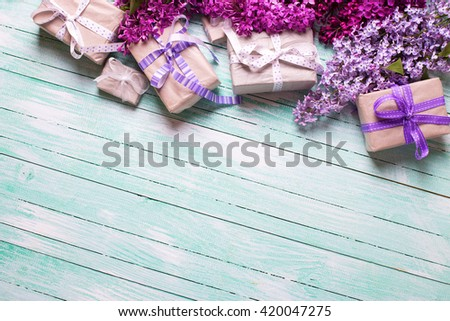 Festive gift boxes with presents  and lilac flowers on turquoise  wooden background. Selective focus. Place for text. - stock photo