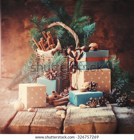Festive Gifts with Boxes, Coniferous, Basket, Cinnamon, Pine Cones, Walnuts on Wooden Background. Christmas Presents Toned in Vintage Style - stock photo