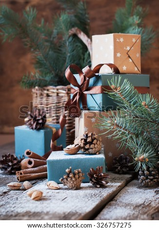 Festive Gifts with Boxes, Coniferous, Basket, Cinnamon, Pine Cones, Walnuts on Wooden Background. Vintage Style - stock photo