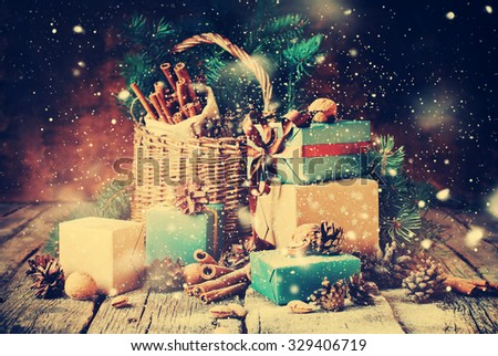 Festive Gifts with Boxes, Coniferous, Basket, Cinnamon, Pine Cones, Walnuts on Wooden Background. Vintage Style with Drawn Snowfall - stock photo