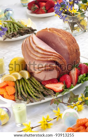 Festive glazed ham for Easter celebration dinner garnished with asparagus, carrots, strawberry, and lemon wedges. - stock photo