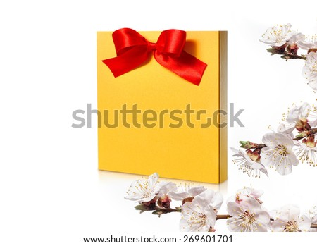 festive gold box with a red bow on a white background - stock photo