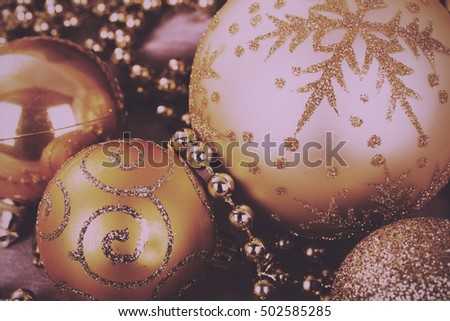 Festive gold Christmas decorations on a fabric background Vintage Retro Filter.