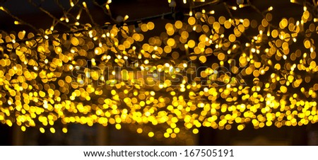 Festive gold garland in urban city decorations for new year and Christmas - stock photo