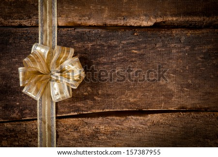Festive gold ribbon and bow border to the left of the frame over a grunge dark textured rustic wood background with copyspace for your Christmas, anniversary or birthday wishes or invitation - stock photo