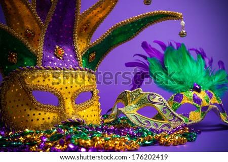 Festive Grouping of mardi gras, venetian or carnivale mask on a purple background - stock photo