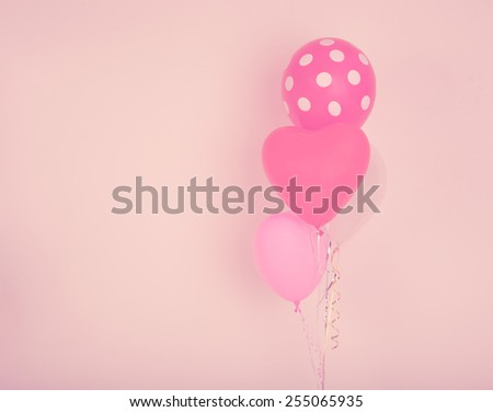 Festive heart shape balloons on pink wall with vintage filter effect - stock photo
