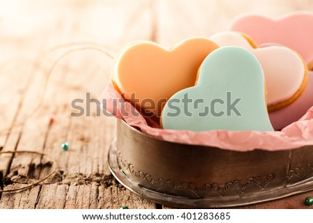 Festive heart shaped fondant cookies with colorful glazing on a rustic wooden table with copy space to celebrate Valentines Day, anniversary or wedding - stock photo
