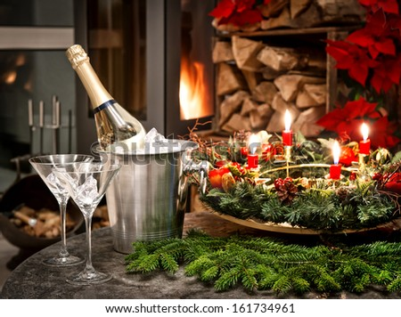 festive home interior decoration for christmas and new year with bottle of champagne and fireplace. candlelight dinner - stock photo