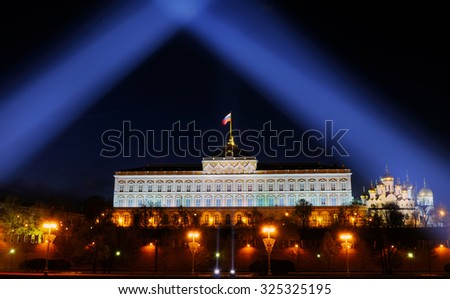 Festive illumination of the Moscow Kremlin at night. Beams of searchlights shine over the Grand Kremlin Palace and the Russian flag. - stock photo