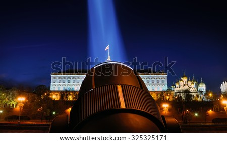Festive illumination of the Moscow Kremlin at night. The beam of a searchlight lights the Grand Kremlin Palace and the Russian flag. - stock photo