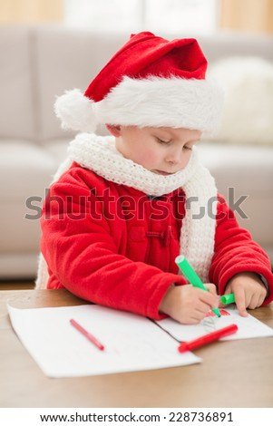 Festive little boy drawing pictures at home in the living room - stock photo