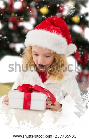 Festive little girl looking at gift against snow falling