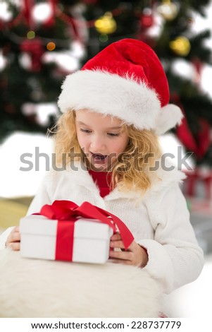 Festive little girl looking at gift on white background