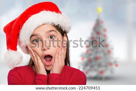 Festive little girl looking surprised against blurry christmas tree in room - stock photo
