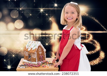 Festive little girl making gingerbread house against christmas light design - stock photo