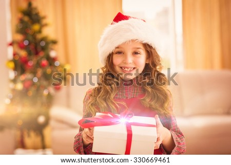 Festive little girl opening a gift at home in the living room - stock photo