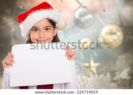Festive little girl showing card against blurred christmas background - stock photo